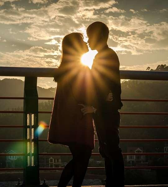 Alma gêmea como reconhecer - Casal de pé se beijando ao por do sol