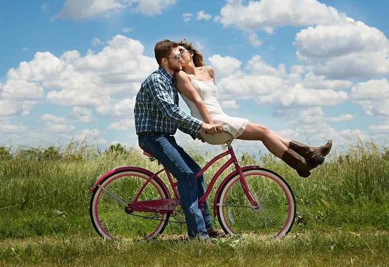 O que são almas gêmeas? Casal de namorados andando de bicicleta.